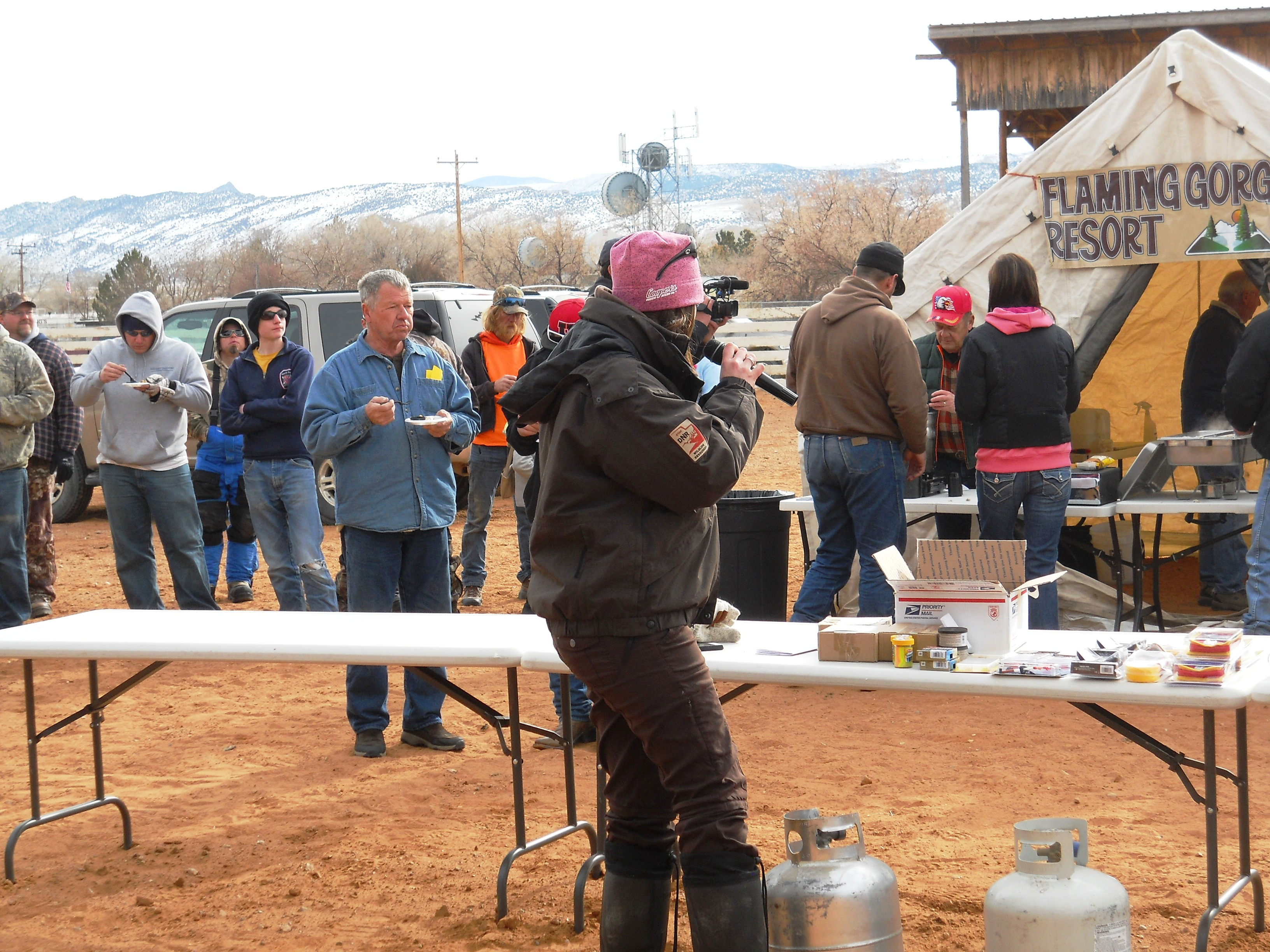 Photo of Tonya Kieffer of KSL's Utah Outdoors makes announcements while Burbot Bash participants enjoy burbot prepared by the Flaming Gorge Resort.