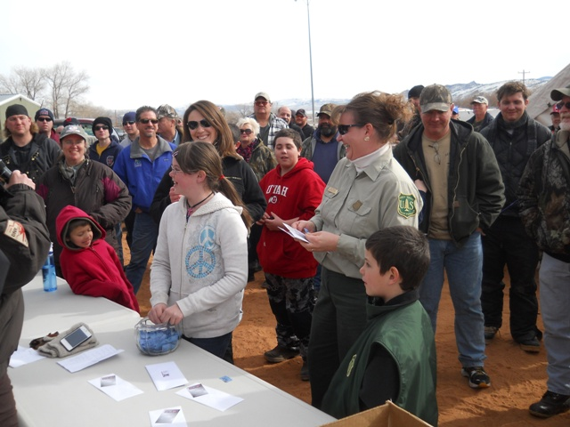 Photo of a young lady drawing a prize ticket during the 2013 Burbot Bash.