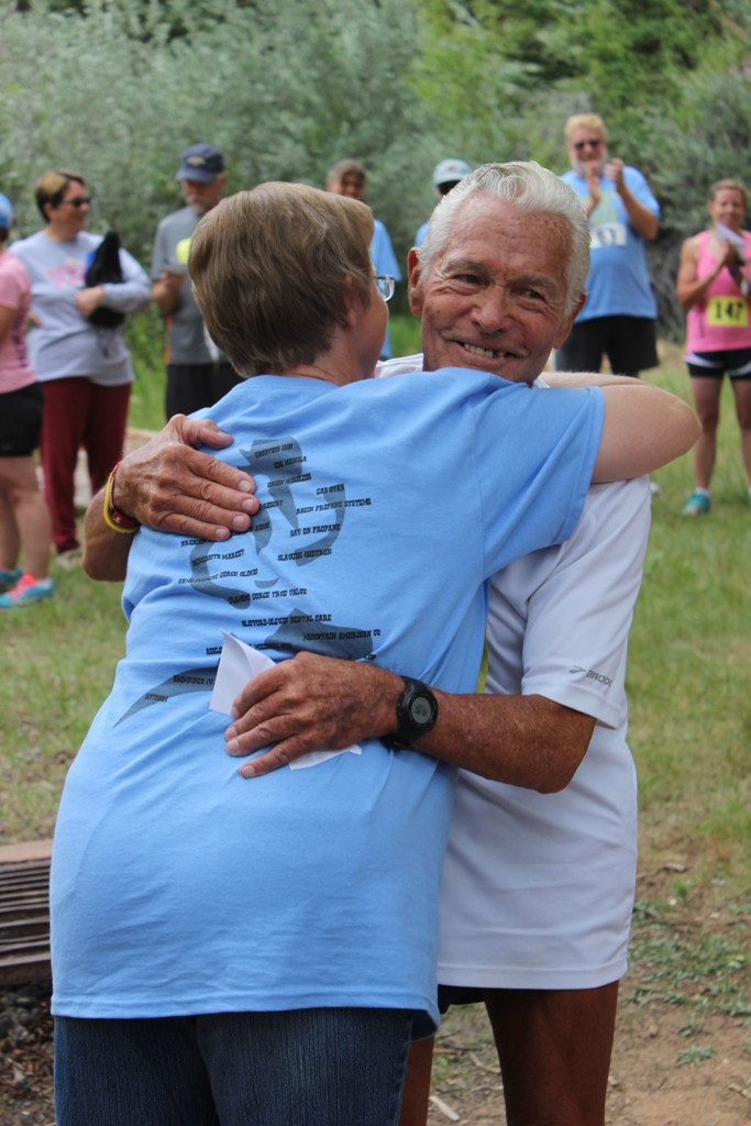 Photo of Currie Harlacher (age 86) and Race Director Sue Morgan hug after the awards