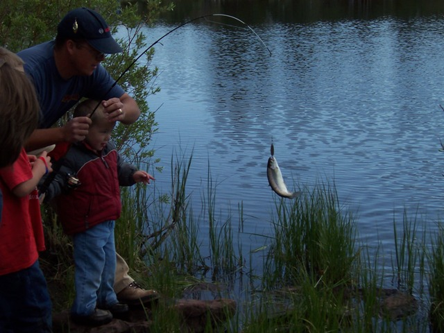 Photo of a fish dangling from the line as its be landed during the 2006 Kid's Fishing Derby at the Moose Ponds.