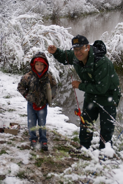 Photo of child and US Forest Service worker holding fish caught during a snowstorm in JUne as part of the annual Kid's Fishing Derby at the Moose Ponds